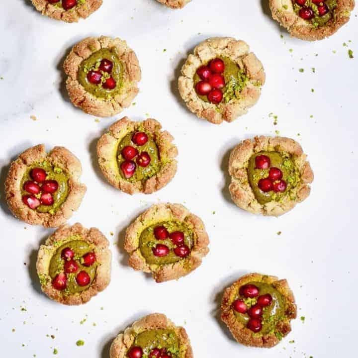 Twelve thumbprint cookies with pistachio butter and pomegranate seeds