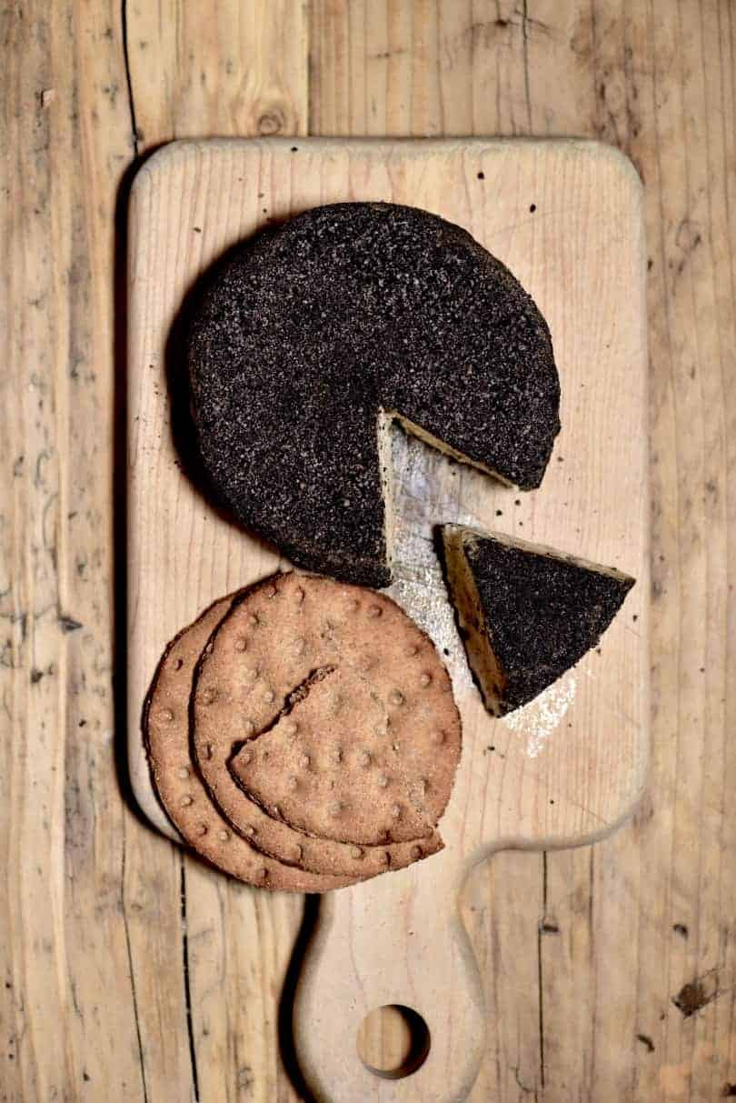 Homemade cashew cheese round with a slice cut off and a few crackers on a wooden board