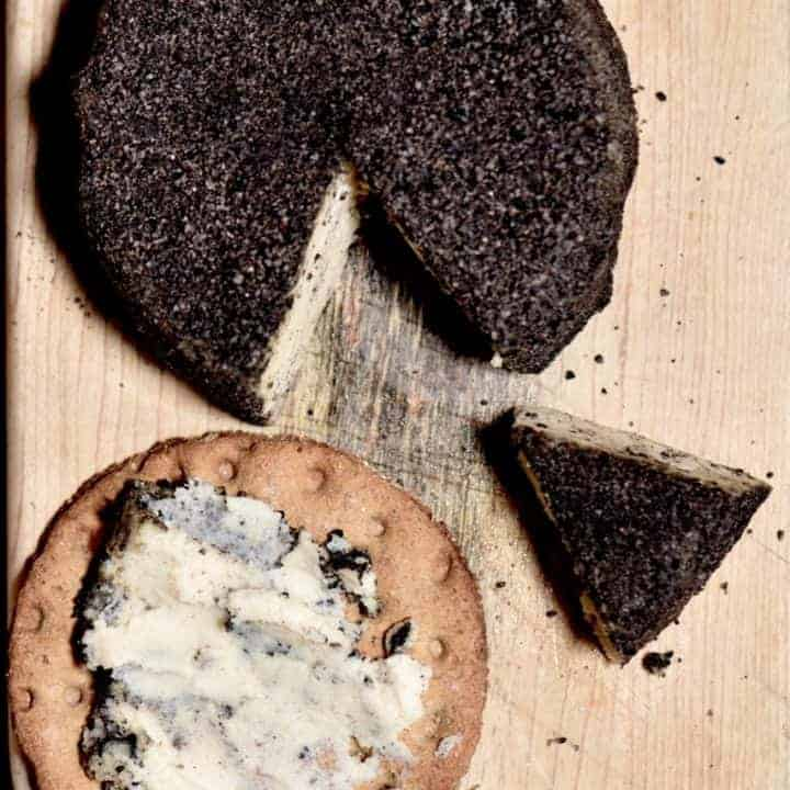 Homemade cashew cheese round with a slice cut off and some spread on a cracker on a wooden board