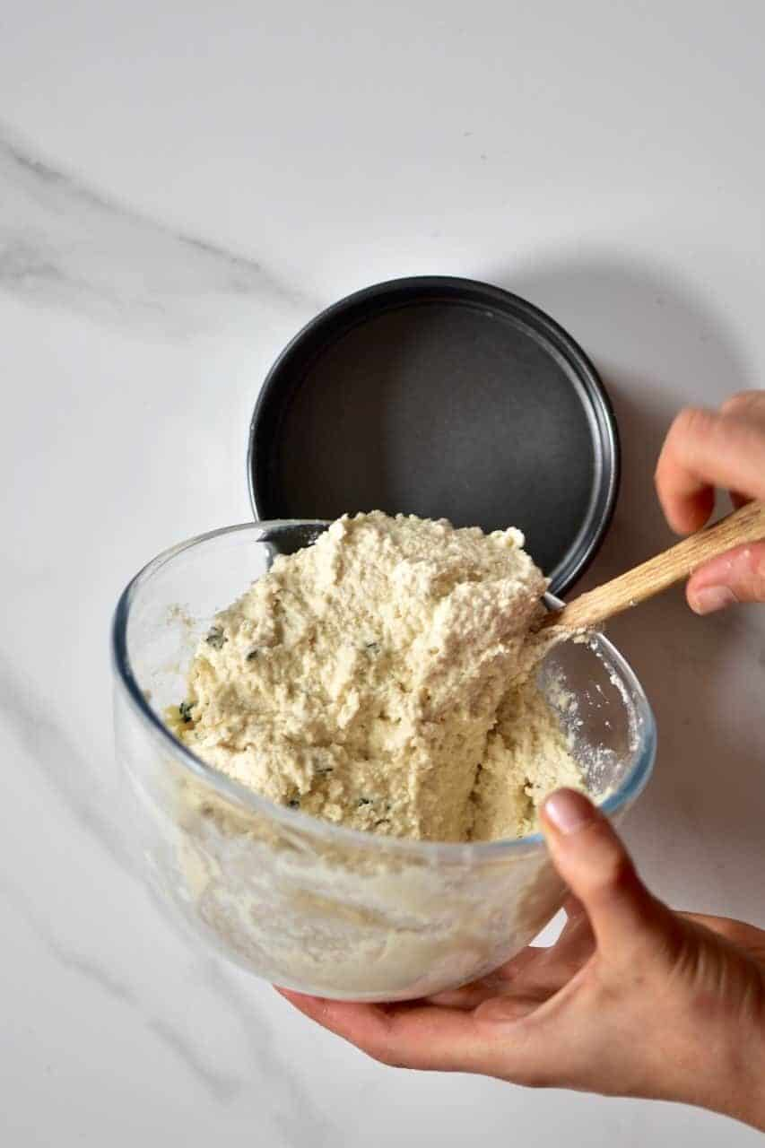 Homemade cashew cheese preparation being moved from a bowl to a mold