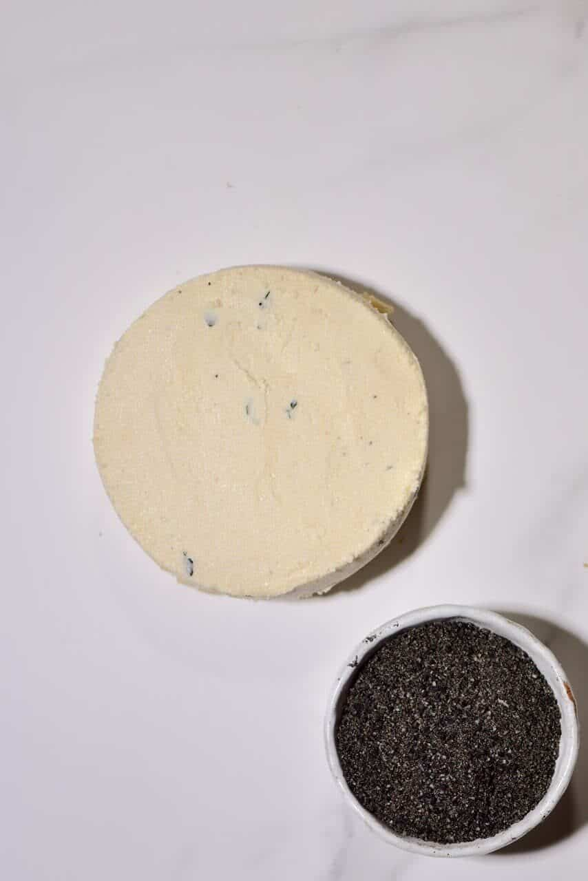 Cashew cheese round and a bowl with nigella seeds