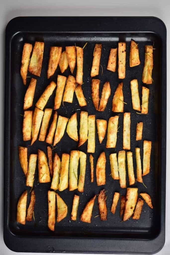 Crispy baked fries on a black tray