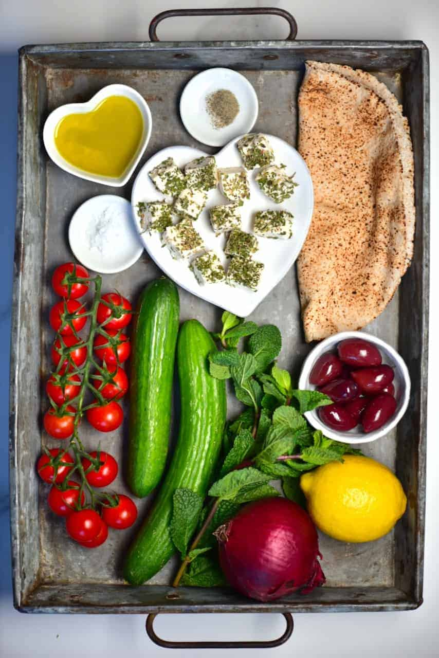 the ingredients to make a homemade vegan greek salad laid out on a tray - olives, cucumber, tomato, mint, vegan feta cheese, lemon olive oil, seasonings and pitta bread