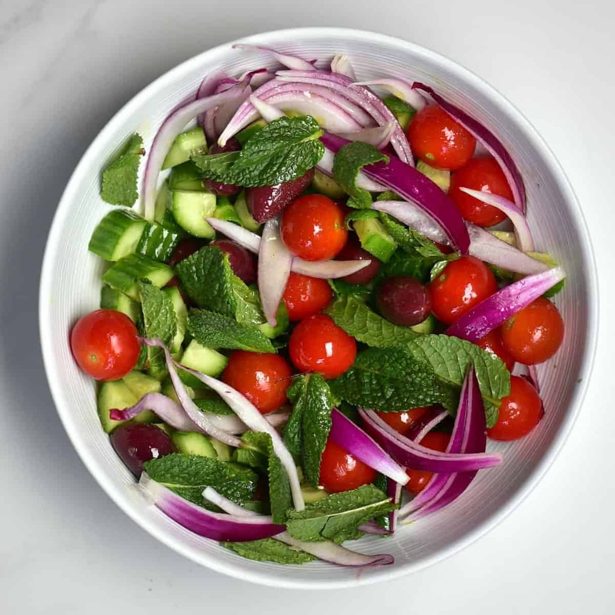 tomato, olives, red onion, cucumber and mint in a bowl