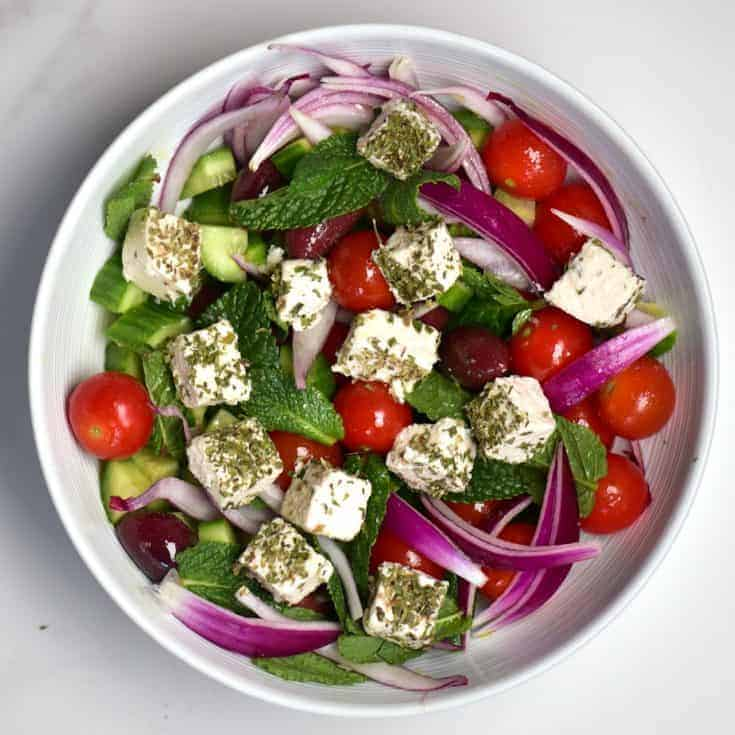 A delicious vegan feta cheese Greek Salad. Just as delicious as it's non-vegan counterpart but with 100% dairy-free vegan feta cheese.Made up of olives, cucumber, tomato, red onion and Mint and a simple extra virgin olive oil based dressing- both a delicious and nutritious meal.