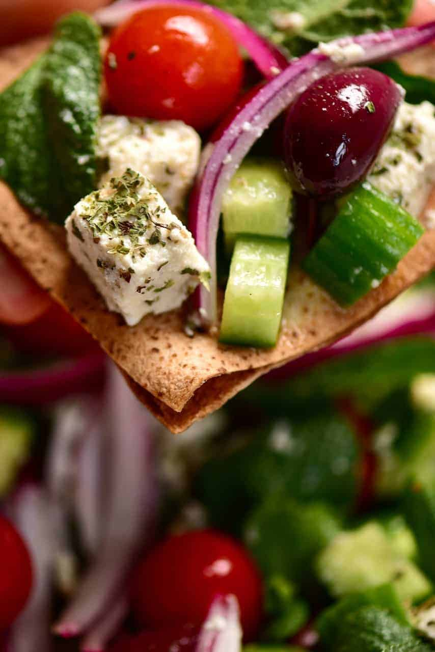 homemade dairy-free, vegan greek salad on top of toasted pitta bread