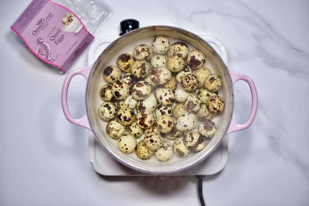 Clarence court quail eggs in a large pot of boiling water