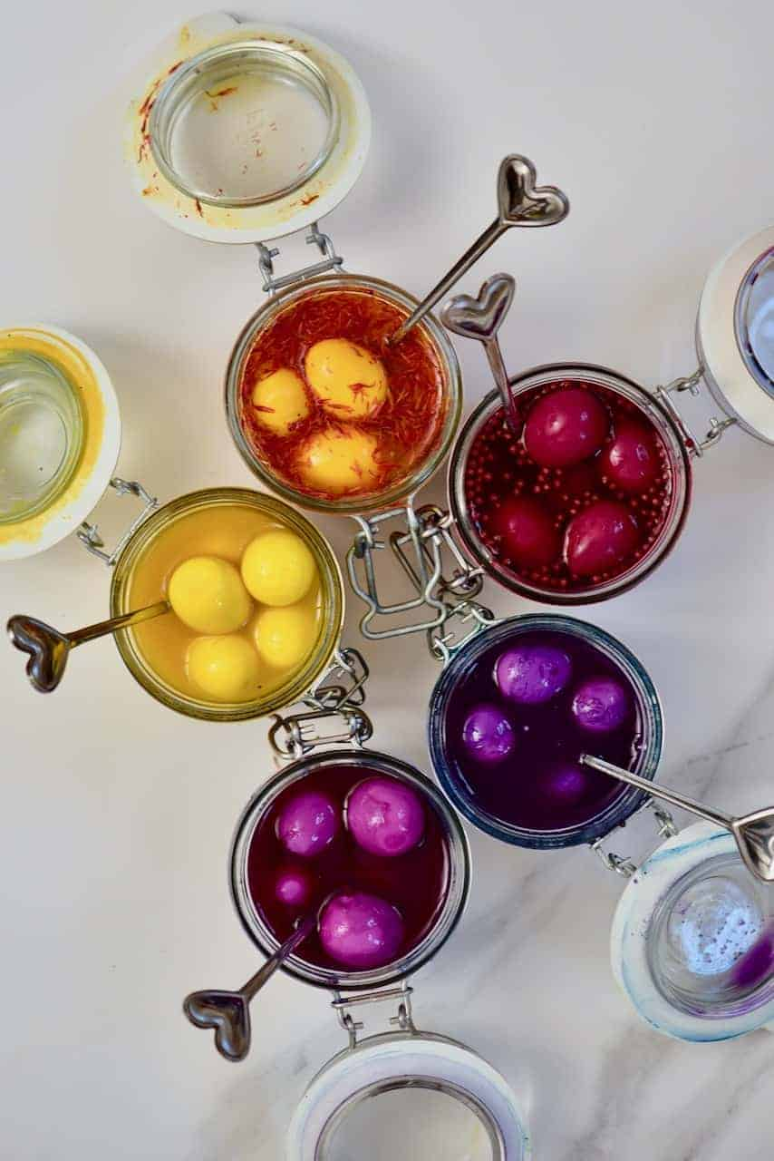 coloured pickled eggs in their pickling liquid - yellow, orange, pink, purple and red