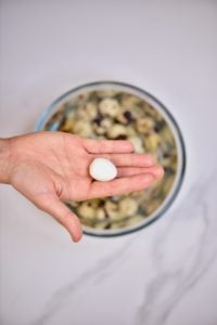 A hand holding one peeled quail egg above a bowl with quail eggs and water
