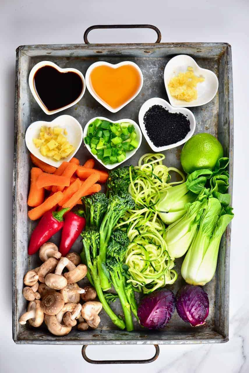 a selection of vegetables and seasoning laid out on a tray, ready to cook a vegetarian ramen