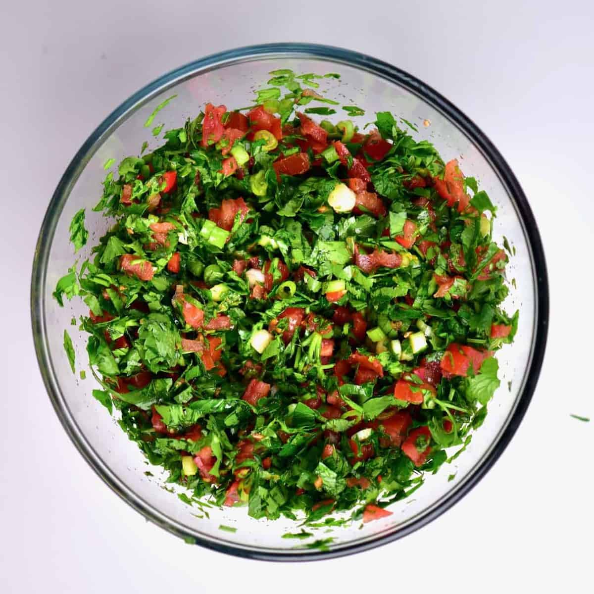 In a bowl, mixed parsley, mint, green onion, chilli and tomatoes for making a Tabbouleh/tabouli salad