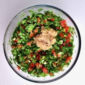 In a bowl, mixed parsley, mint, green onion, chilli, tomatoes and bulgur wheat dressing for making a Tabbouleh/tabouli salad