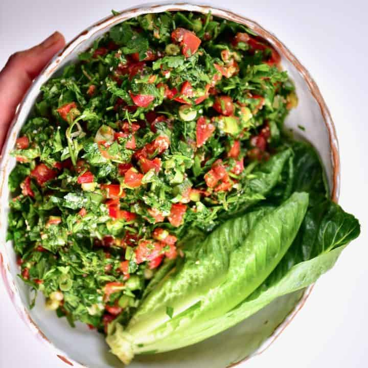 Freshly mixed Tabbouleh/tabouli salad served with romaine lettuce in a bowl
