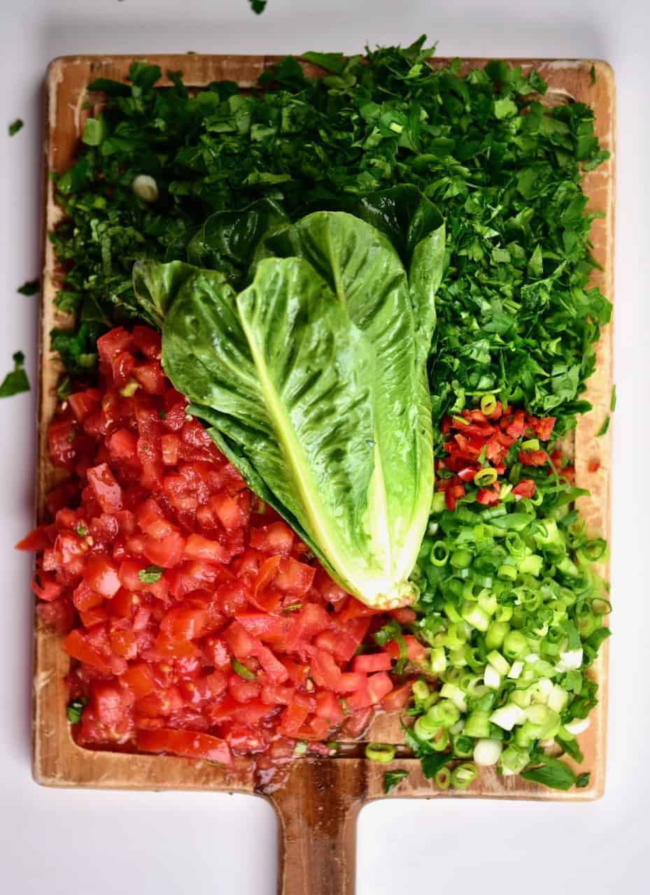 chopped tomato, green onion and parsley on a chopping board