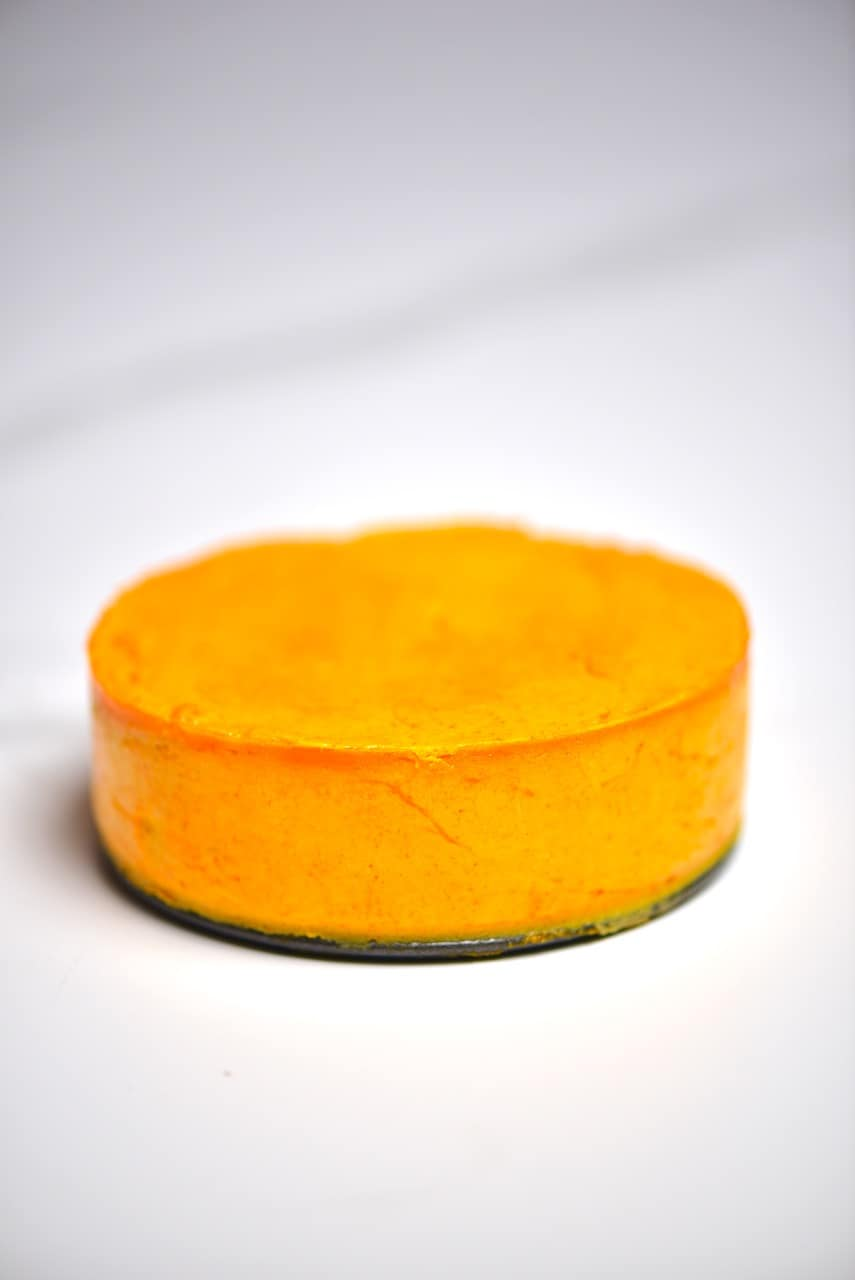 A round of homemade vegan cheddar cheese