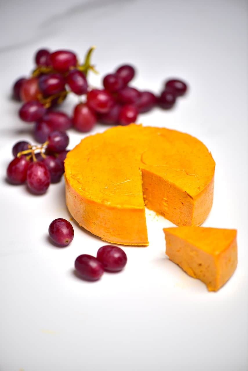 Vegan cheddar cheese with some red grapes