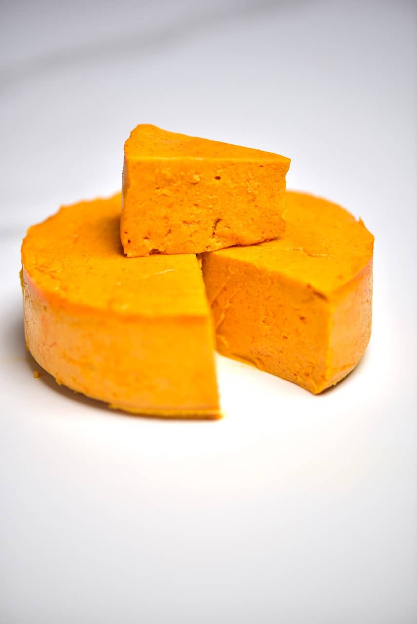Vegan homemade cheddar cheese with a cut slice
