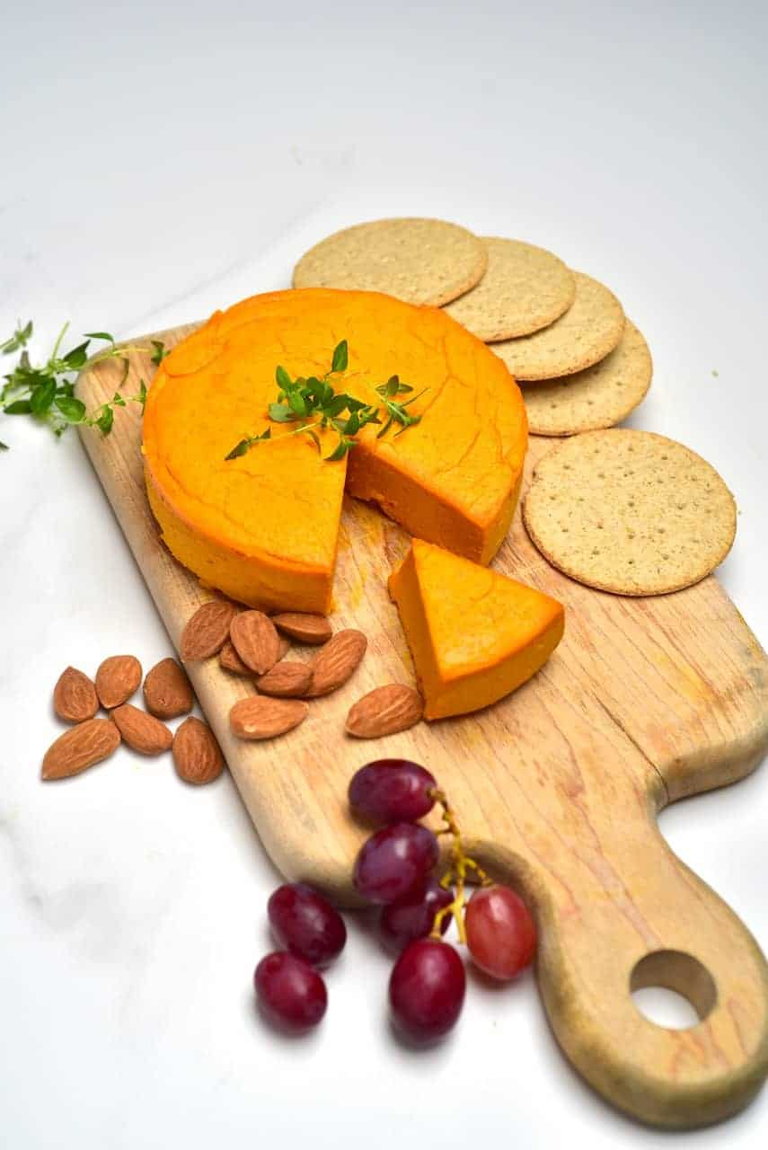 Homemade vegan cheddar cheese eon a board with crackers almond and grapes
