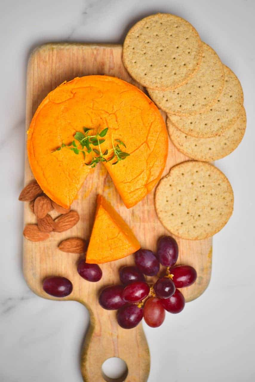 Vegan cheddar cheese with some crackers and grapes on a cutting board