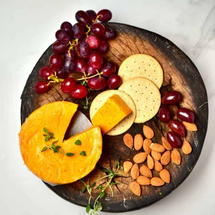 Homemade vegan cheddar cheese served with red grapes, almonds and crackers
