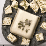 A Simple Tangy, Herby Vegan Feta Cheese Recipe. A wonderfully crumbly dairy-free cheese that's perfect for salads and topping all sorts of dishes.