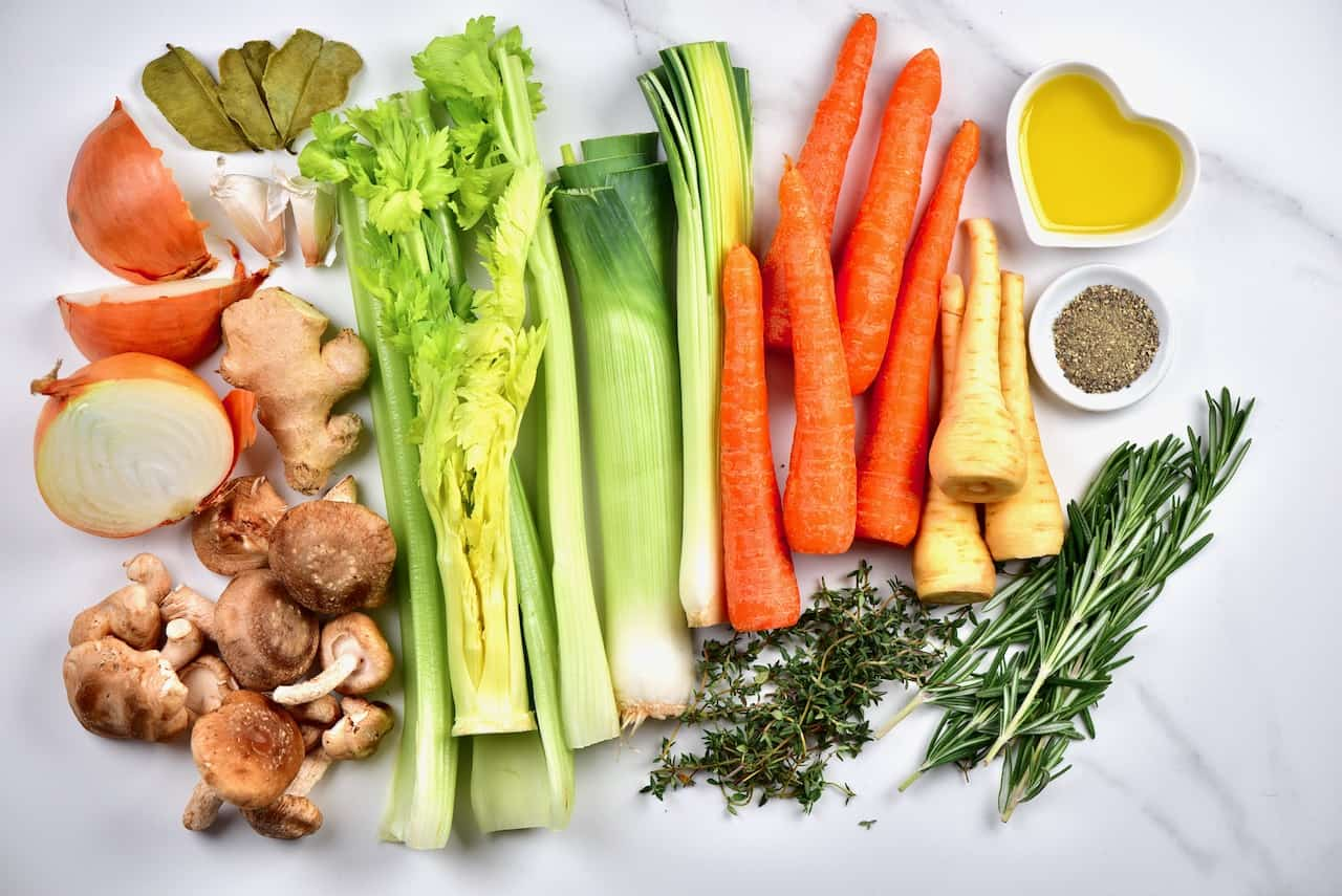 the ingredients for a delicious homemade vegetable stock including carrots, parsnips, mushrooms, celery, onion, garlic, ginger and a variety of herbs