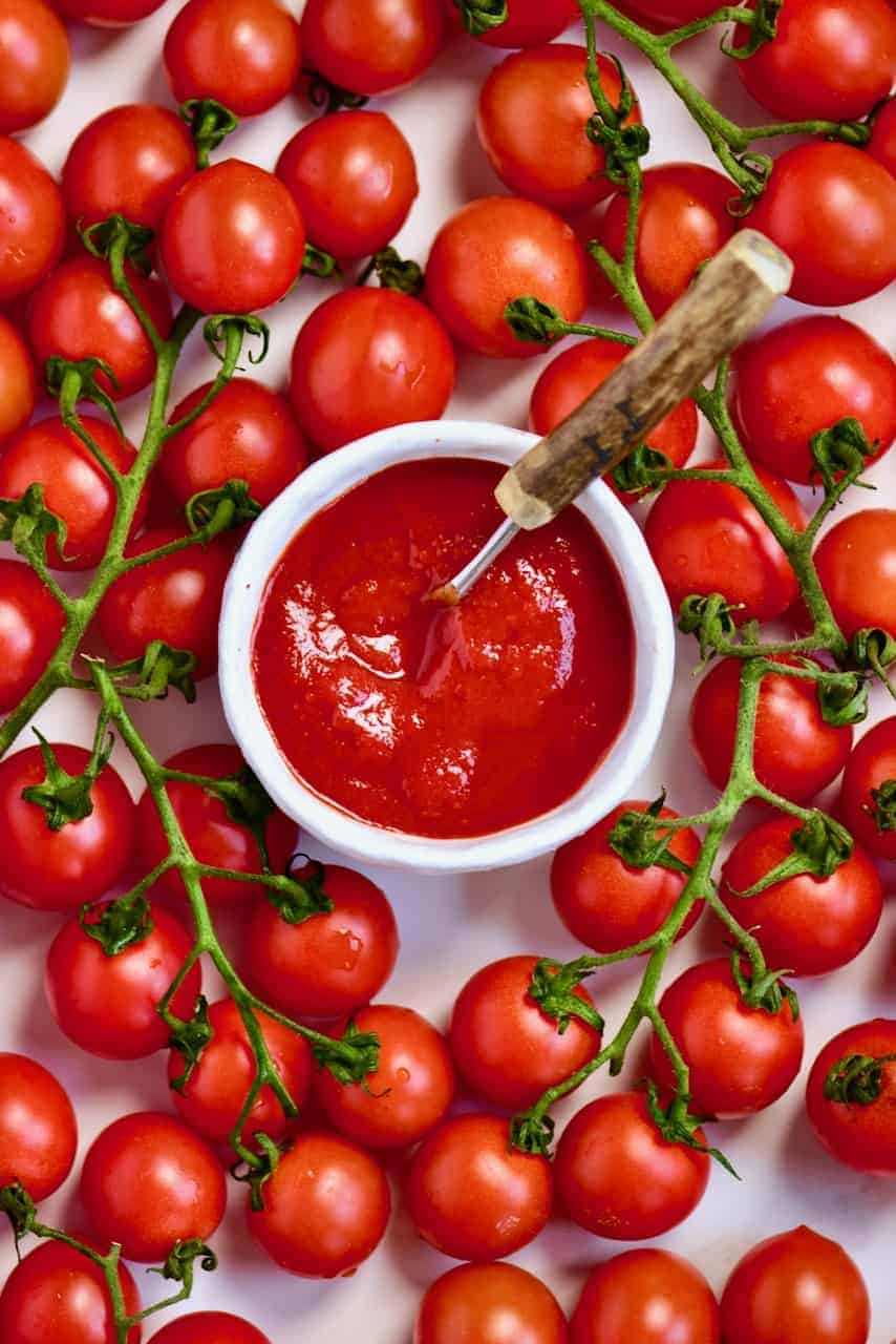 homemade ketchup in a bowl and a tomato bunch