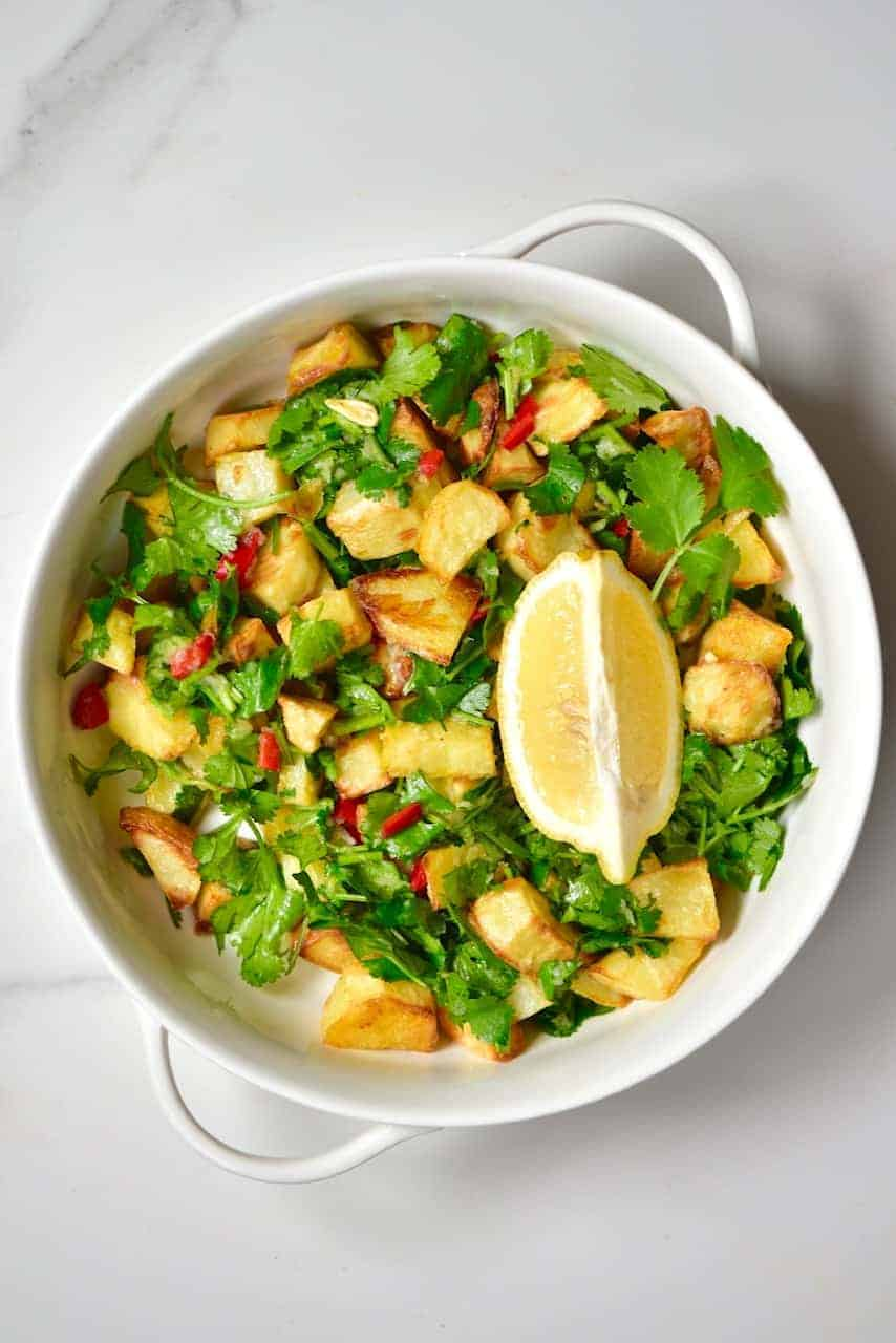 Lebanese spicy potatoes, Batata Harrah ( batata harra ) served with lemon wedge