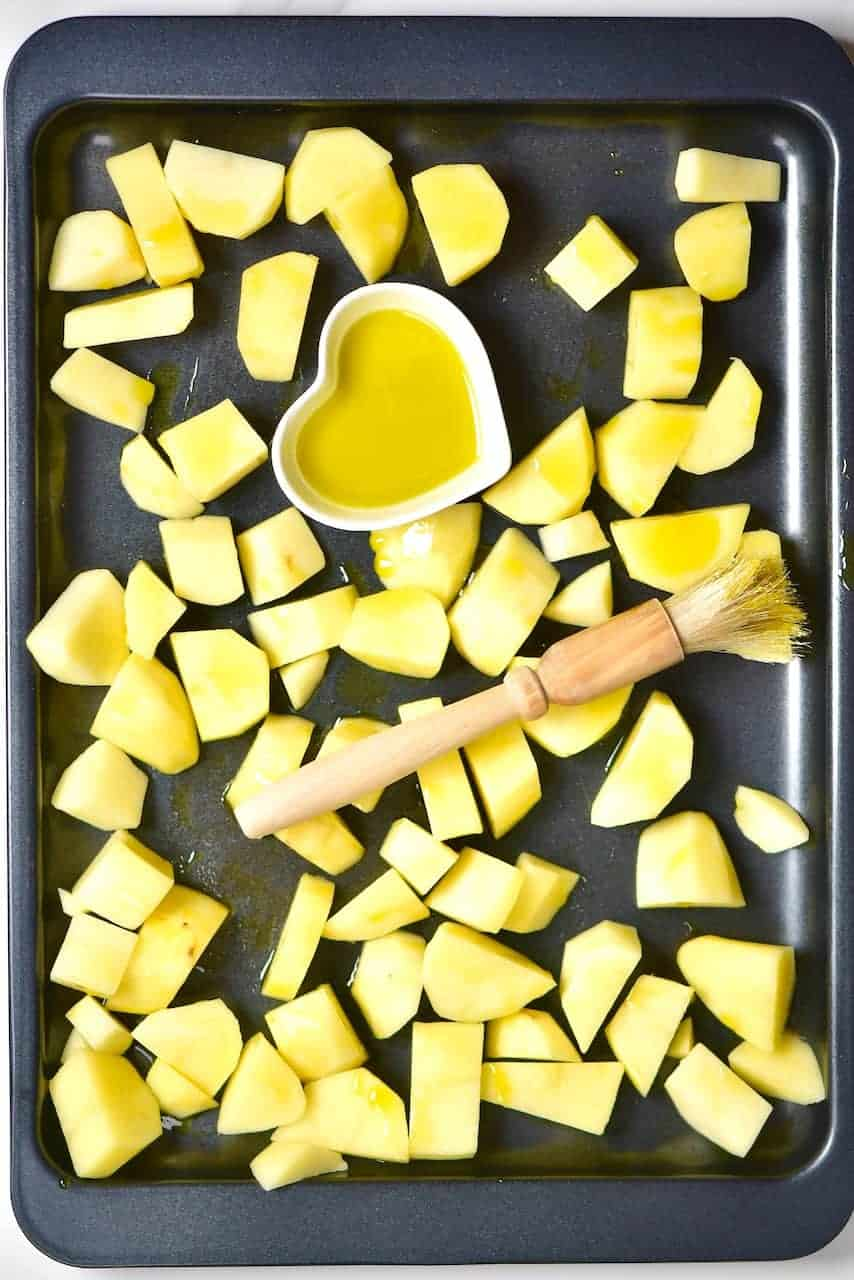 Coating chopped potatoes with olive oil