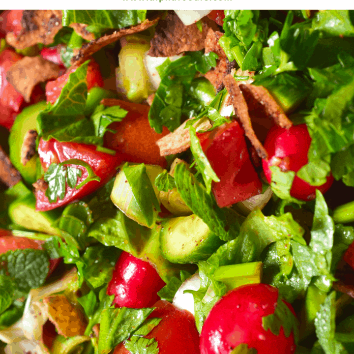 A close up of fattoush salad with mint cucumber tomatoes and toasted pita bread