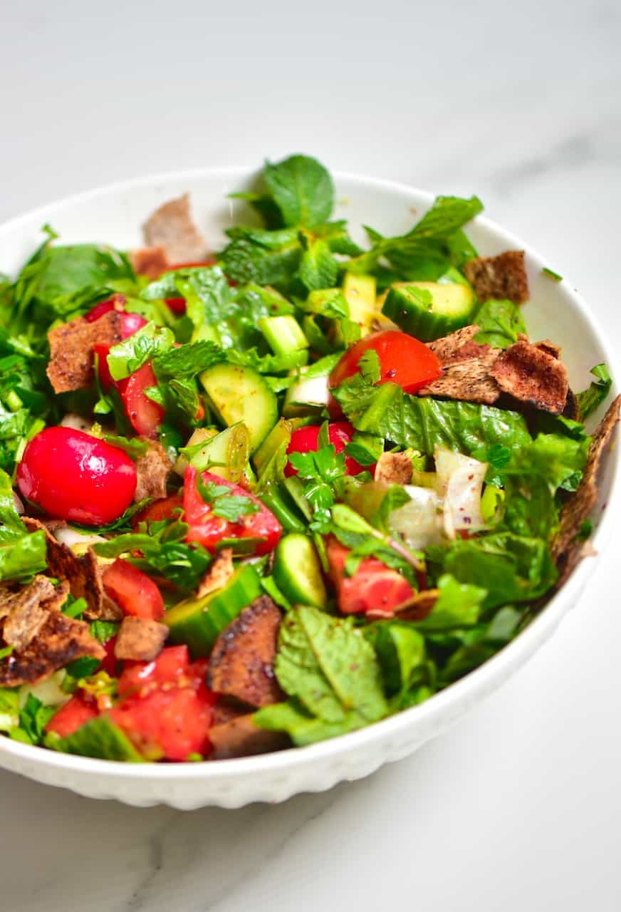 fattoush salad in a white bowl on top of marble table