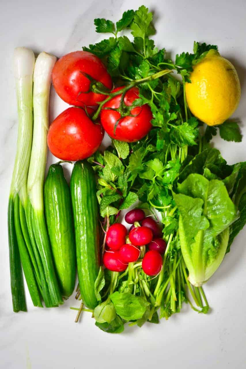 ingredients for a salad including spring onions, cucumber, radish, mint, parsley, lettuce, tomatoes, lemon