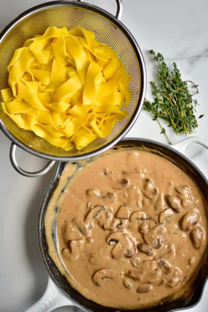 a pan of creamy mushroom pasta sauce and colander with pappardelle pasta