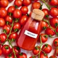 Homemade ketchup in a bottle and tomatoes