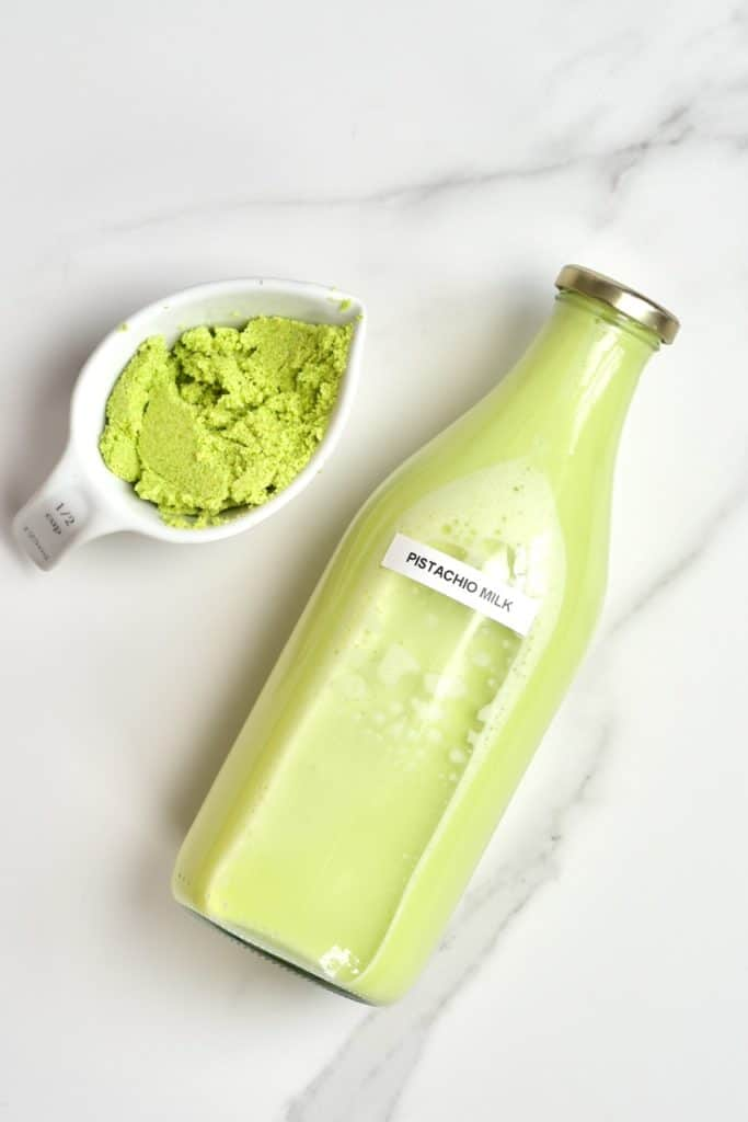 homemade pistachio in a bottle and some leftover nut meat - DIY pistachio milk recipe