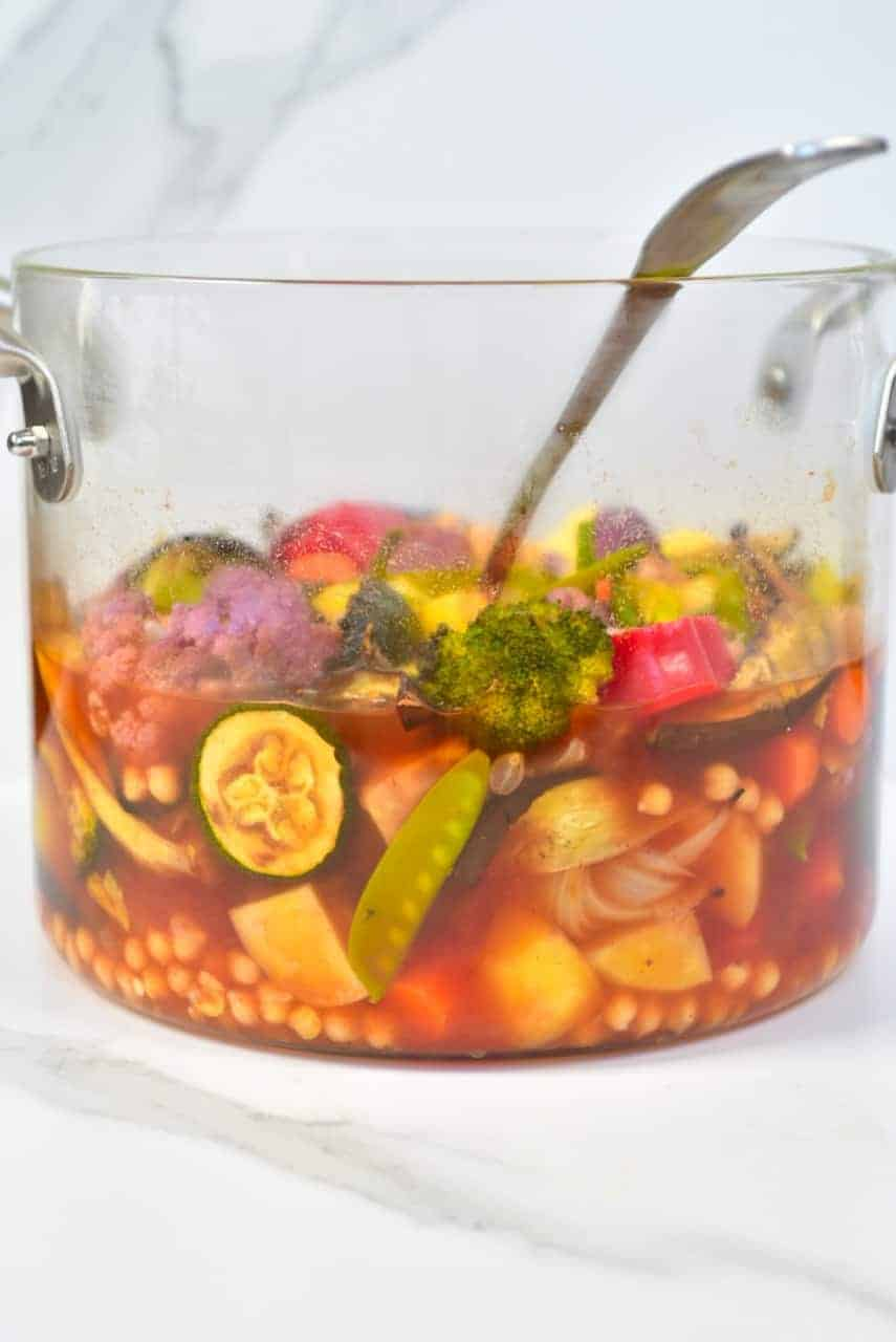 Rainbow vegetable chickpea stew in a glass pot