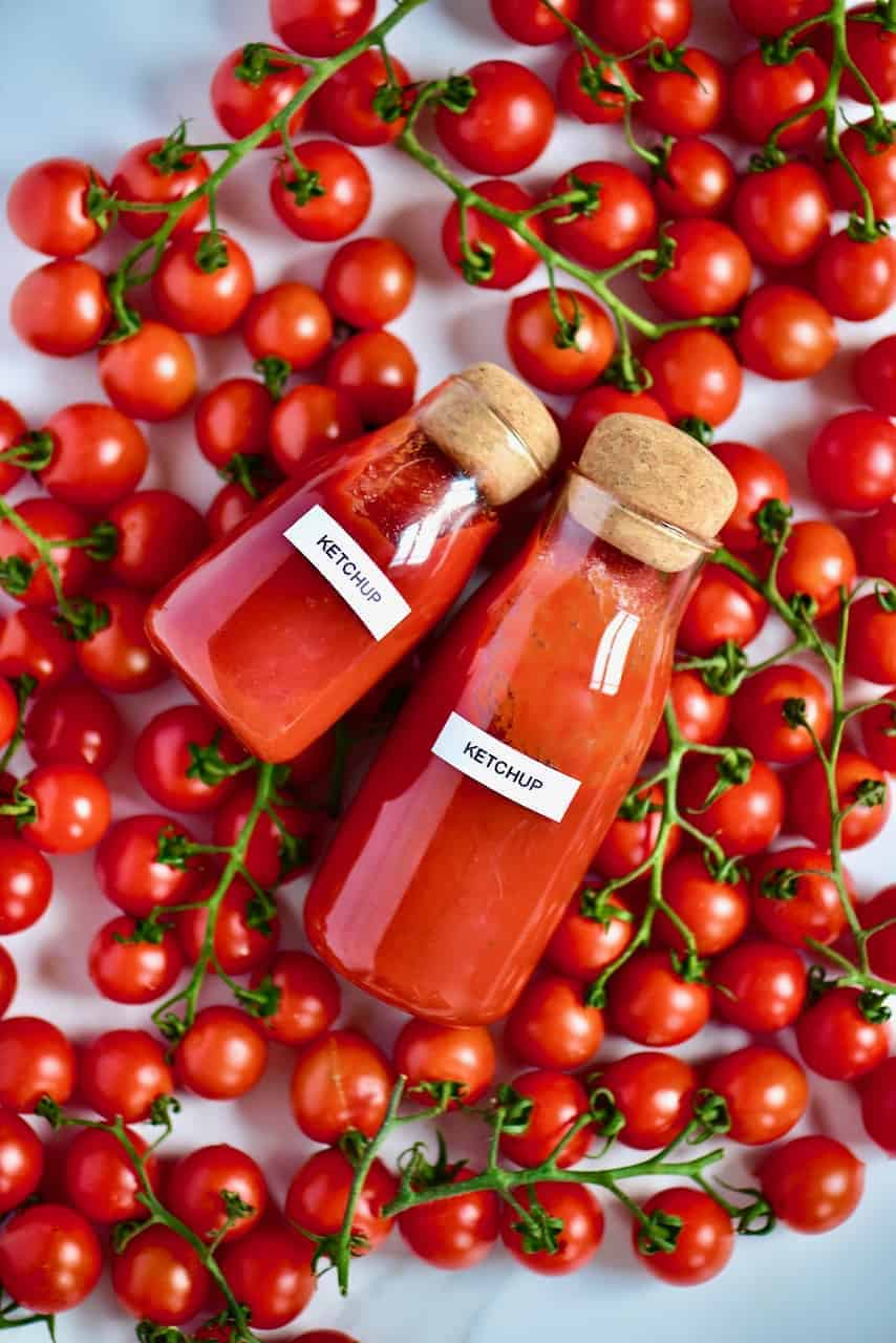 Two bottles of homemade ketchup and a bunch of tomatoes