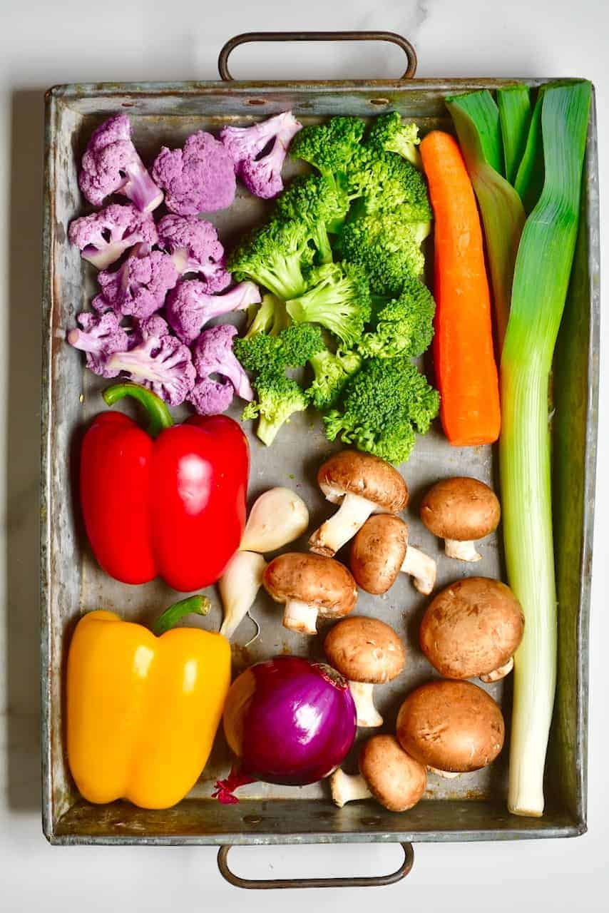 a selection of rainbow vegetables on a tray for a vegan pasta bake