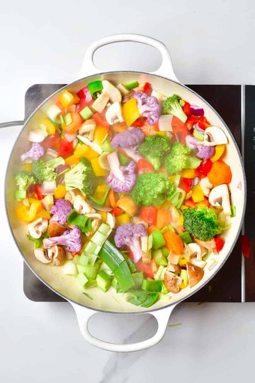 frying and steaming rainbow vegetables in a large pan