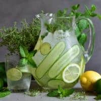 Flavored water jug with herbs, lime and lemon and glass