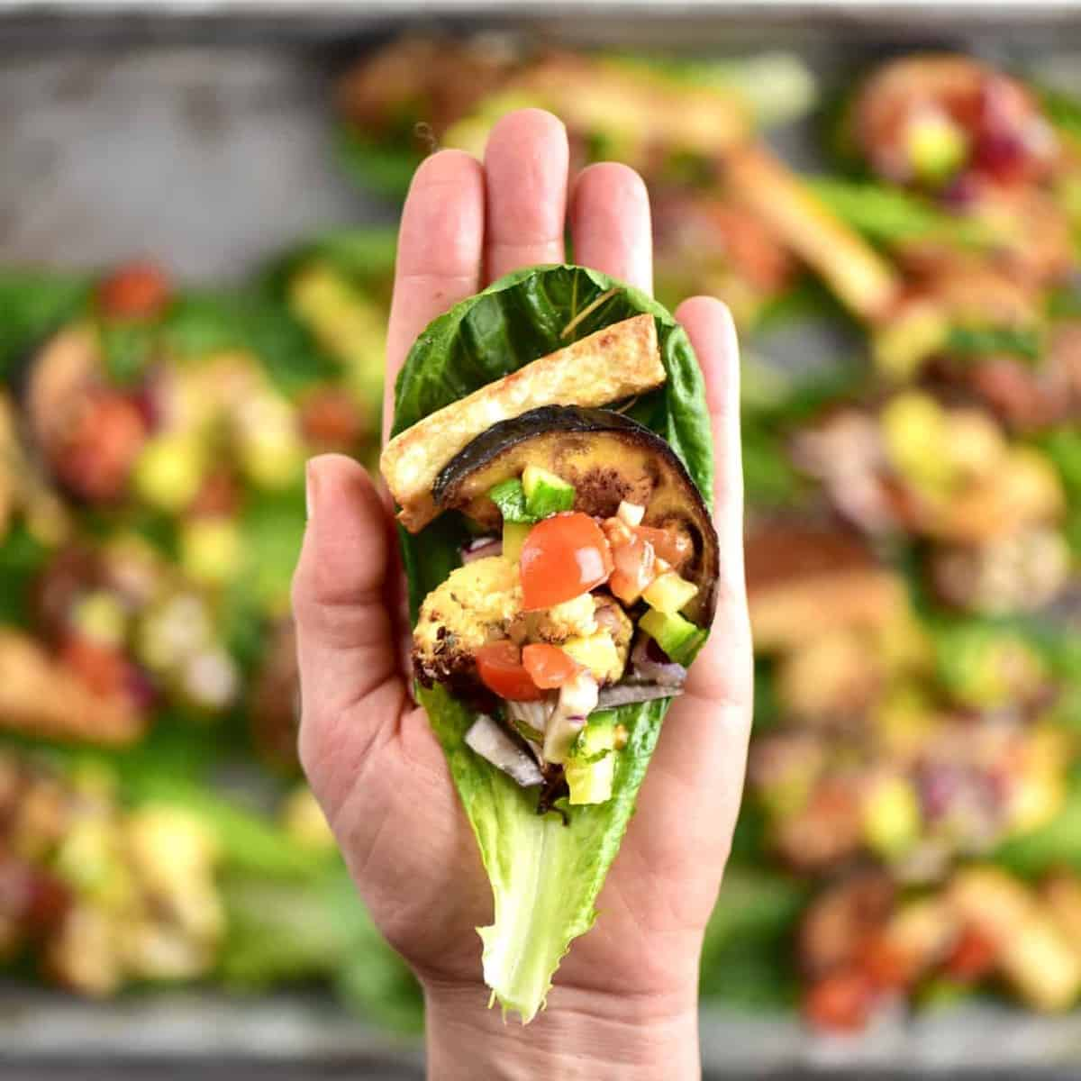 holding lettuce boat in hand with Mediterranean veg