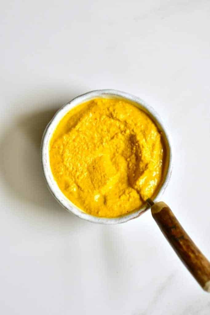 A bowl of mustard and spoon