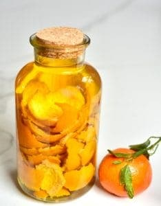 A jar filled with vinegar and citrus peel