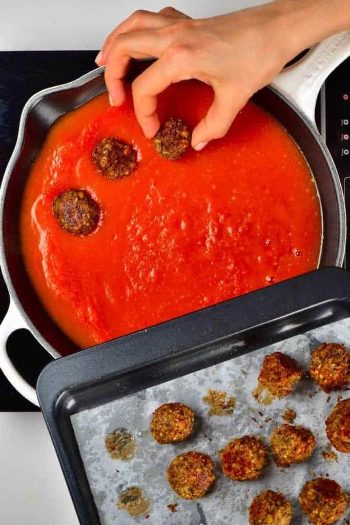 Arranging lentil meatballs in tomato sauce