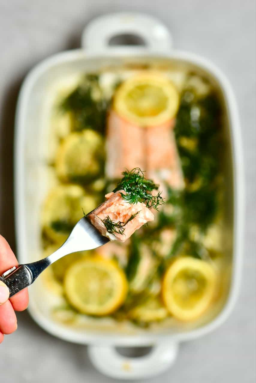 A close up of baked salmon with dill and lemon