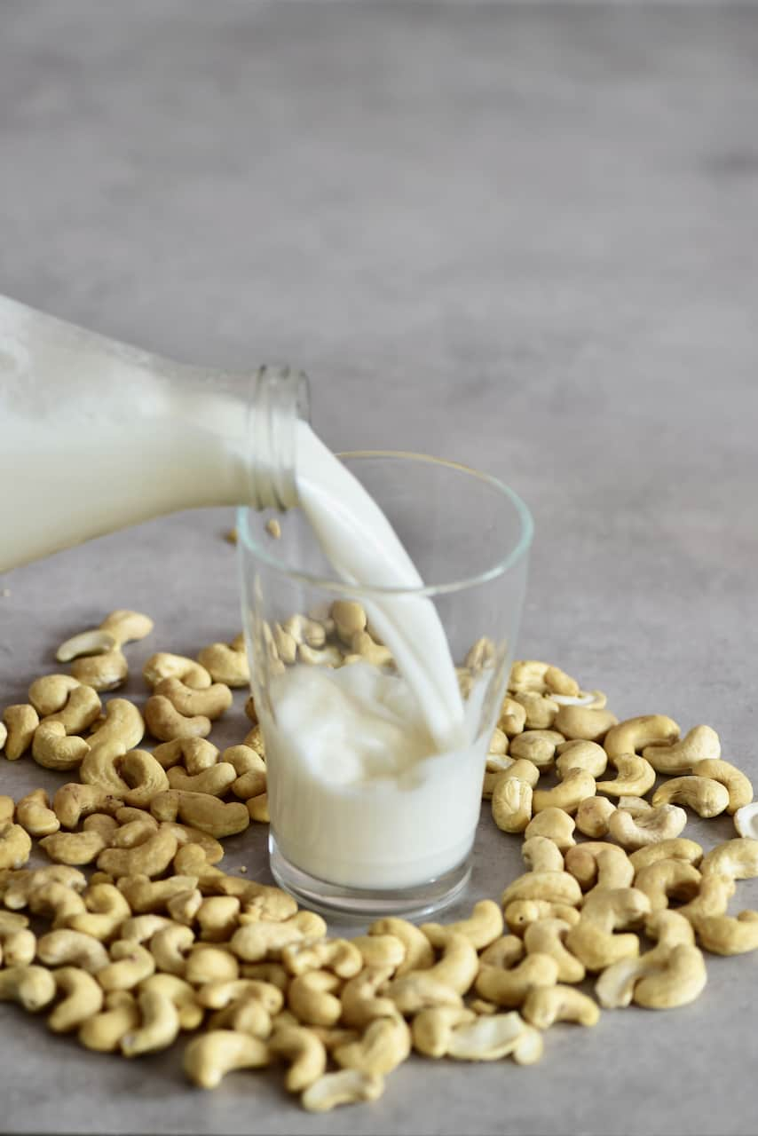 Pouring cashew milk in a glass