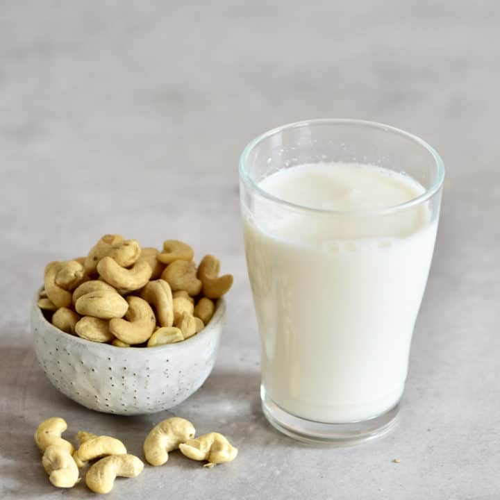 Cashew milk in a glass and a bowl of cashews