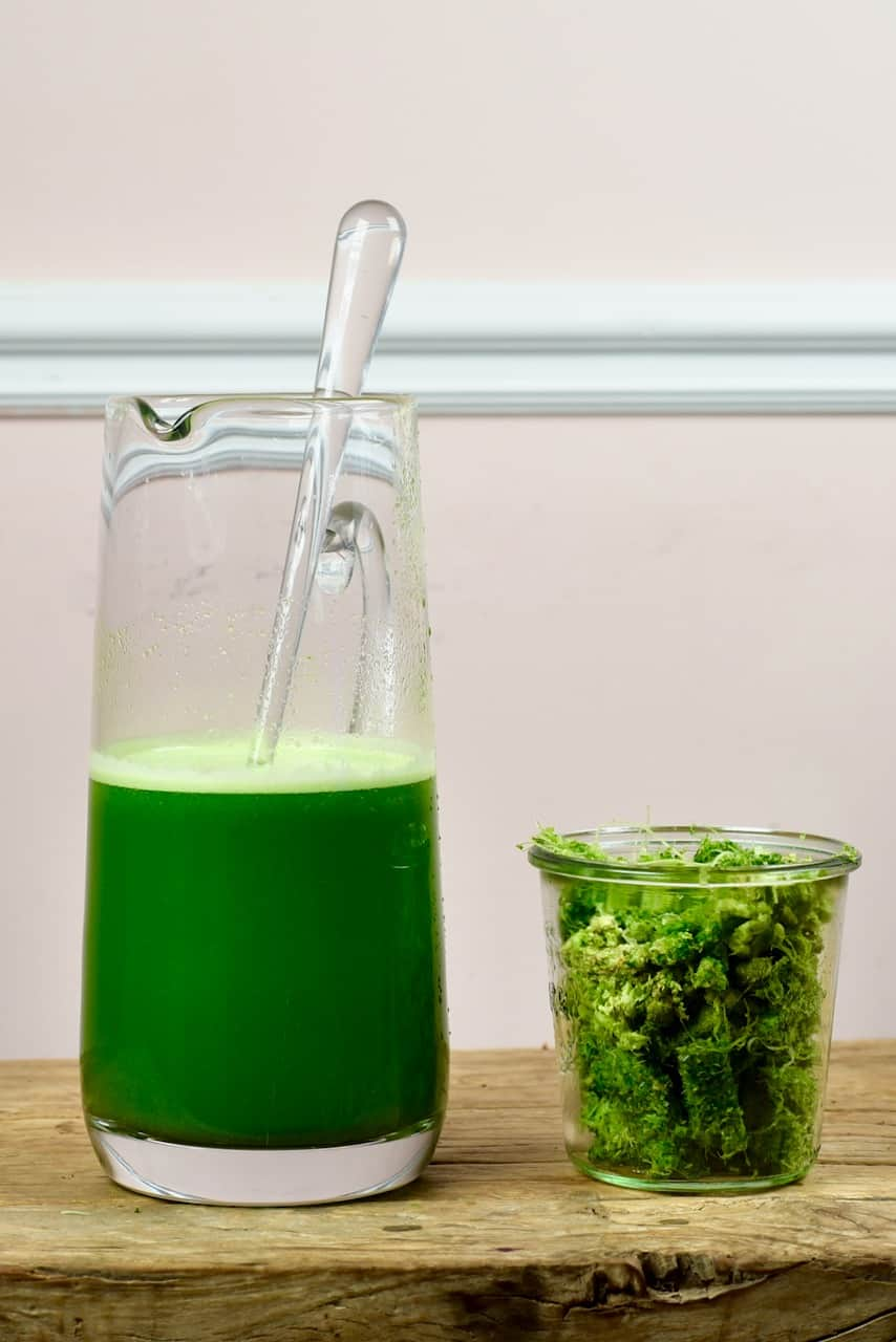Celery juice in a pitcher and leftover fibre