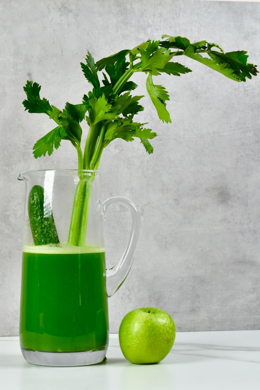 Celery juice with cucumber and apple next to it