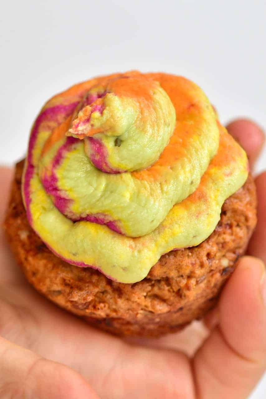 Close up of a cupcake with rainbow hummus frosting
